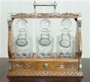 Sale 8338A - Lot 53 - An Edwardian carved oak three bottle tantalus, with silver plated mounts, with key, W 36 x H 36cm