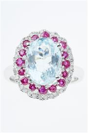 Sale 8338J - Lot 350 - AN 18CT WHITE GOLD AQUAMARINE AND GEMSET RING; centring an oval cut aquamarine of 3.17ct to surround of 16 round cut rubies encircle...
