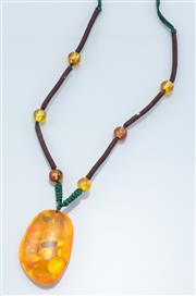 Sale 9037F - Lot 36 - A LARGE INSECT AMBER PENDANT NECKLACE; 36 x 54mm freeform reconstituted amber inserted with a bee to brown and green plaited adjusta...