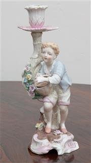 Sale 9070H - Lot 71 - A German porcelain figural candlestick of a boy and basket with blue cross sword marked to base, Height 25cm