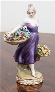 Sale 9070H - Lot 72 - A German porcelain figure of a lady in a purple dress carrying baskets of spring flowers, Height 26cm