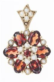 Sale 8293 - Lot 357 - A GARNET AND PEARL FLORAL CLUSTER PENDANT; set in 9ct gold with oval and round cut almandine garnets and seed pearls, length 25mm.