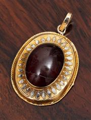 Sale 9070H - Lot 77 - A 14ct gold pendant of pierced oval form set with a cabochon garnet (cracked) wt 4.38g