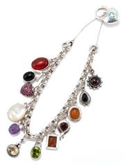 Sale 9066 - Lot 318 - A SILVER GEMSET CHARM BRACELET; belcher chain attached with 12 assorted charms set with carnelian, onyx, synthetic rubies, mother of...