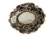 Sale 8457 - Lot 372 - A VICTORIAN GOLD CASED MOURNING BROOCH; central plaited hair compartment to black enamel surround with gold foliate feature and scro...