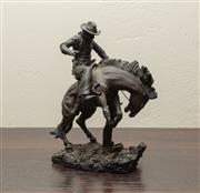 Sale 8871H - Lot 177 - A bronze effect cowboy statue (broken foot), after Fred Remington Height 34cm
