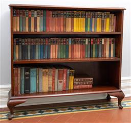 Sale 9256H - Lot 71 - An Australian cedar slimline bookcase raised on short cabriole legs, H 99cm x W 110.5cm x D 25cm, includes a quantity of mainly vint...
