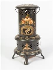 Sale 8651A - Lot 47 - An Australian early 1900s Valour Junior kerosene heater with original kero tank and wick fitting. The black exterior enhanced with s...