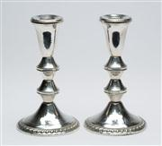 Sale 8444A - Lot 95 - A pair of sterling silver candlesticks with embossed rims, H 16cm