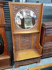 Sale 8728 - Lot 1027 - Edwardian Oak Hall Seat, the high mirror back carved with dragons & fish, above a hinged seat with fantastic beasts below