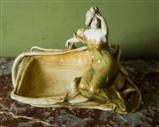 Sale 8418A - Lot 27 - An Austrian porcelain fruit bowl with an Art Nouveau maiden perched to the edge, L 50cm, damages