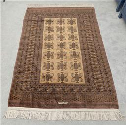 Sale 9256H - Lot 23 - An Afghan hand knotted wool rug of fine quality, with a repeating geometric motif in brown tones, signed, 126cm x 188cm.
