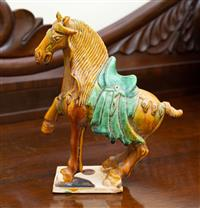 Sale 8735 - Lot 94 - A Tang style horse in ochre and green glaze, H x 24cm