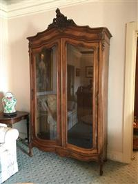 Sale 8392H - Lot 57 - A French Walnut armoire in the Louis XV manner with later glass shelves.