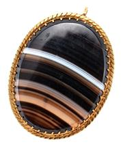 Sale 9054 - Lot 377 - A VINTAGE 18CT GOLD BANDED AGATE PENDANT; cut down claw set with a 38 x 29mm agate of bands in brown black and white to a pie crust...