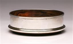 Sale 9110 - Lot 65 - A contemporary sterling silver wine bottle coaster with wood-turned base, London marks for c1991 (Dia:13cm)