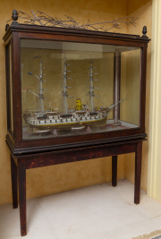 Sale 8677B - Lot 510 - A timber scale model of HMS Victoria complete with six stand alone life boats, encased in a timber display cabinet, resting on a non...