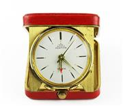 Sale 8402W - Lot 63 - PONTIFA TRAVEL ALARM CLOCK; round white dial with recessed gilt markers, centre seconds, fold out clock in 40 x 48mm red leatherette...