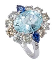 Sale 9037 - Lot 385 - AN AQUAMARINE DIAMOND AND SAPPHIRE CLUSTER RING; bead claw set in 18ct white gold with an oval cut aquamarine of approx. 3.3ct to su...