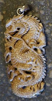 Sale 8319 - Lot 21 - Mammoth ivory pendant in the form of a dragon.