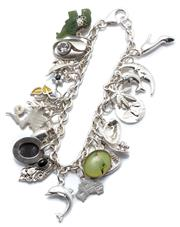 Sale 9046 - Lot 319 - A SILVER CHARM BRACELET; cable link chain with parrot clasp attached with various charms incl nephrite elephant and mother of pearl...