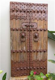 Sale 8644A - Lot 1 - A pair of antique Balinese metal and timber doors with mask ring pull handles, H 180 x W 92cm.