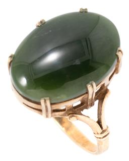 Sale 9149 - Lot 301 - A VINTAGE 9CT GOLD NEPHRITE RING; set with an oval cabochon nephrite (18.12 x 12.70mm) above pierced gallery and split shoulders, si...