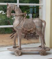 Sale 8677B - Lot 536 - A vintage distressed teak horse on cart, Height 118cm