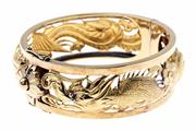 Sale 8400 - Lot 390 - AN 18CT GOLD HINGED BANGLE; centring dragon motif to a box clasp with twin safety clips. Width 22mm, internal diam. 60mm. (stamped 2...