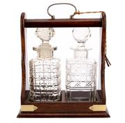 Sale 8897 - Lot 69 - An Edwardian timber tantalus, with plated hardware encasing two non-matching cut crystal decanters, with keys, H 31 x W 25cm