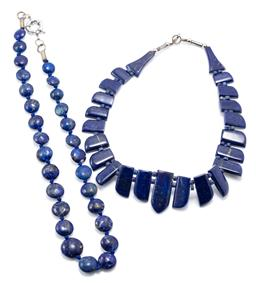 Sale 9169 - Lot 355 - TWO GRADUATED LAPIS NECKLACES; 11-18mm button lapis beads, length 55cm, and other 14-35mm shaped lapis plaques, length 43cm, both to...