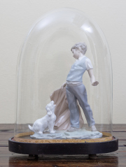 Sale 8677B - Lot 578 - A Nao figure of a boy and dog displayed in an antique cloche, total height 38cm