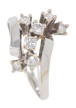 Sale 9160 - Lot 396 - A RETRO STYLE 18CT WHITE GOLD RING; featuring bypass shoulders long pillar claw set with 7 round brilliant cut diamonds totalling ap...
