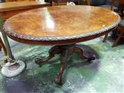 Sale 8653 - Lot 1068 - Victorian Burr Walnut Loo Table, the oval tilt-top with carved edge, on a turned carved pedestal with outwept feet