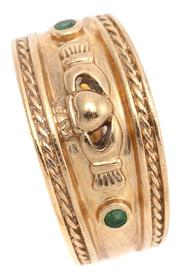 Sale 9095 - Lot 309 - A 9CT GOLD CLADDAGH RING; tapered band (9.8 - 4.5mm) rub set with a small emerald either side of the clasped hands and heart to rope...