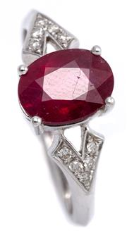 Sale 9095 - Lot 330 - AN 18CT WHITE GOLD RUBY AND DIAMOND RING; centring a treated oval cut ruby adjacent to chevron shape shoulders each set with 5 round...