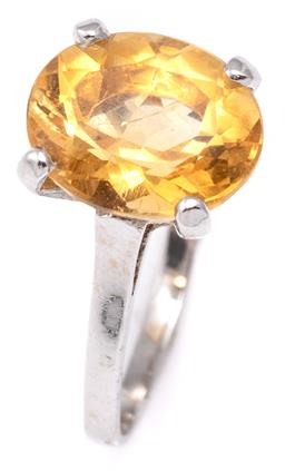 Sale 9115 - Lot 333 - AN 18CT GOLD SOLITAIRE CITRINE RING; 4 claw set with an oval cut citrine of approx. 3.62ct, rhodium plated over 18ct yellow gold, si...