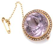 Sale 9083 - Lot 355 - AN ANTIQUE 15CT GOLD AMETHYST AND PEARL BROOCH; millegrain set with an approx. 29ct round cut light amethyst (diam. 21.5mm) to a sur...