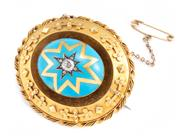Sale 8899 - Lot 361 - A VICTORIAN DIAMOND AND ENAMEL BROOCH; featuring a 23 x 19mm blue enamel oval shape platform star set with an approx. 0.30ct Old Eur...