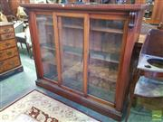 Sale 8539 - Lot 1049 - Victorian Mahogany Dwarf Bookcase, with three sliding glass panel doors, flanked by pilasters & on plinth base (slight veneer loss)