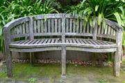 Sale 8568A - Lot 6 - A teak kidney shaped outdoor bench, missing one slat, W 151cm