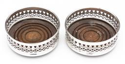 Sale 9245R - Lot 43 - A pair of English hallmarked sterling silver bottle coasters, Nat Joseph, London 1973, the pierced silver framing the oak base with ...