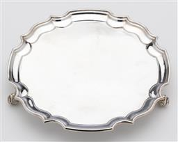 Sale 9245R - Lot 45 - An English hallmarked sterling silver salver, B P Co, Birmingham 1966, with Chippendale border and raised on 3 knurled feet. D: 155m...