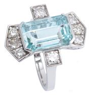 Sale 9066 - Lot 398 - A DECO STYLE PLATINUM AQUAMARINE AND DIAMOND RING; centring an approx. 6.80ct emerald cut aquamarine set at each end and on the upsw...