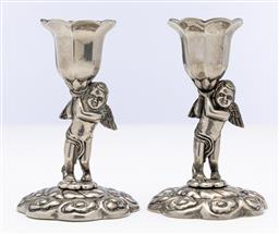 Sale 9245R - Lot 56 - A charming pair of silverplate candlesticks, the floral embossed base centred by an angel holding the candle cup aloft. Ht: 11cm