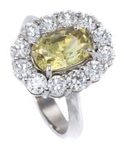 Sale 8937 - Lot 355 - AN ELEGANT CHRYSOBERYL AND DIAMOND CLUSTER RING; centring an approx. 2.10ct green oval cut chrysoberyl surrounded by 12 round brilli...