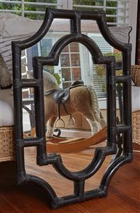 Sale 9080H - Lot 53 - A shaped mirror of seven panel design with a blackened cane frame, 96cm x 68cm