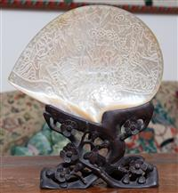 Sale 8963H - Lot 45 - A late Qing/ Republic carved shell with an unusual abstract design of concealed figures and animals on a stylised plum branch stand,...