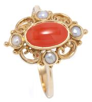 Sale 9066 - Lot 340 - A VICTORIAN STYLE PEARL AND CORAL RING; centring an oval cabochon coral to scrolling 9ct gold surround set with seed pearls, size N1...