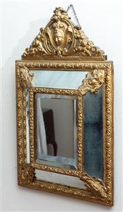 Sale 8804A - Lot 156 - A pressed brass cushion shaped mirror with ornate frame and crest, H 60cm